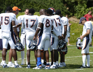 Stefan Fatsis, shown taking notes as wide receivers coach Steve Watson, wearing a cap in the huddle, addresses the Broncos. Photograph by John Leyba.